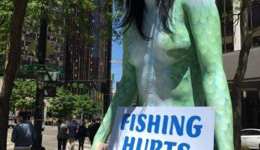 'Sirena' toples enganchada y pendiendo, en protesta de la crueldad de la industria pesquera